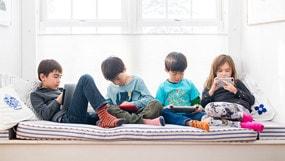 Cuatro niños sentados usando dispositivos conectados a Internet.