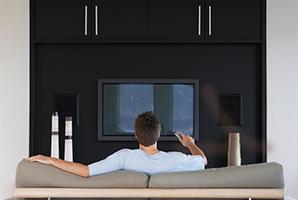 Un hombre en un sofá encendiendo su TV.