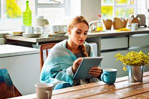 Mujer tomando un café por la mañana con su tablet