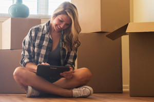 Mujer sentada en el piso con un tablet rodeada de cajas
