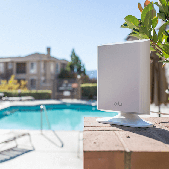 Lifestyle view of the Netgear Orbi Add-on OutdoorSatellite shown poolside on the stand