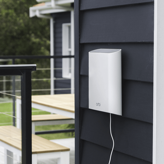Lifestyle view of the Netgear Orbi Add-on Outdoor Satellite Shown mounted to a wall