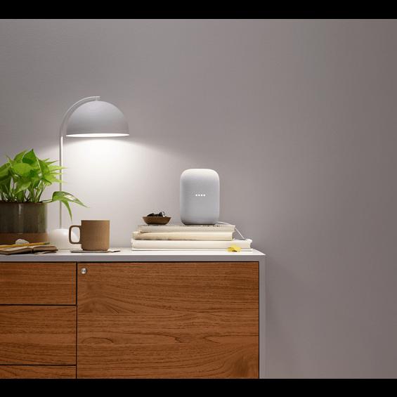 Imagen de estilo de un Google Nest Audio en chalk en un tocador debajo de una lámpara