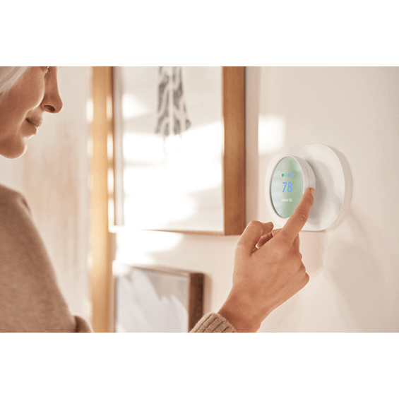 Lifestyle view of Nest Thermostat in cotton white with person making adjustment