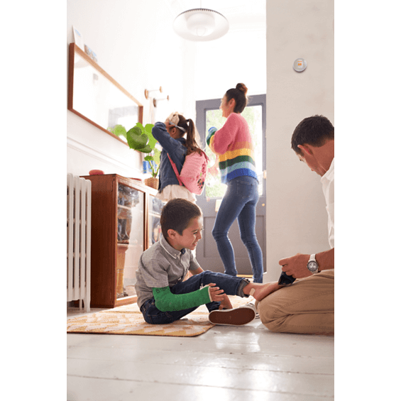 Lifestyle view of Nest Thermostat in cotton white on wall behind kids playing