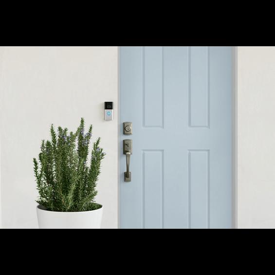 Imagen de estilo de vida del timbre con sistema de video Ring 3 al lado de una puerta azul