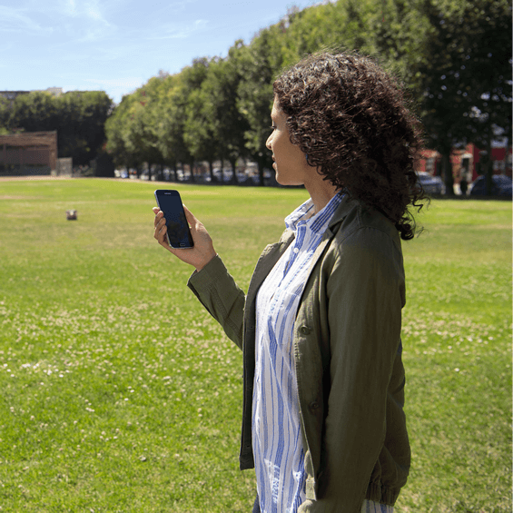Girl looking at a mobile phone in a field